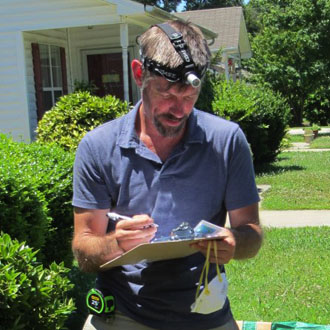 AIM Team Leader Clarke Snell is standing in the homeowner's front yard with a flashlight on his head and a clipboard in his hand.