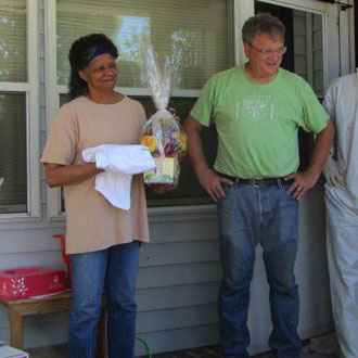 Thomas Gentry stands with the homeowner on her front porch. She is holding a gift basket.